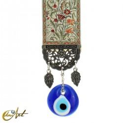Amuleto ojo turco con alfombra base crema.